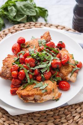 coxas de frango crocantes grelhadas em panela com tomates e manjericão empolados